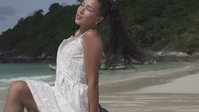 Beautiful girl on tropical island. Beautiful brunette woman in white dress relaxing in the sun on the tropical paradise island beach - video in slow motion stock footage