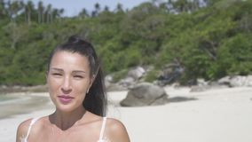 Beautiful girl on tropical island. Closeup face of beautiful brunette woman in white dress smiling and looking into the camera while running on the tropical stock video footage