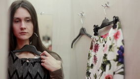 Beautiful girl trying clothes in a fitting room stock footage