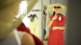 Beautiful girl trying clothes near mirror on room background. Young woman wearing funny hat and sunglasses. Happy stock video