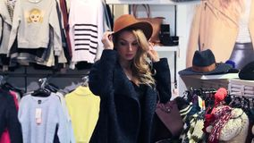 Shopping. Beautiful girl trying on a hat in a clothing store. Beautiful girl trying on a hat in a clothing store stock video footage