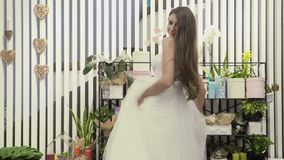 Beautiful girl in white dress is turning around herself at flowers background. Beautiful girl is turning around near the stand with pots with flowers. Charming stock footage