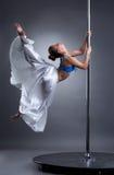 Beautiful girl turning gracefully around pylon Stock Photos