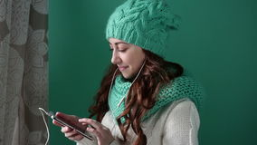 Beautiful girl in a turquoise knitted hat listening to music stock video