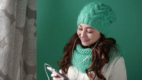 Beautiful girl in a turquoise knitted hat listening to music stock video footage