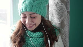 Beautiful girl in a turquoise knitted hat listening to music stock footage