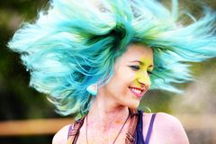 Beautiful girl twirls by head during Holi color festival. Portrait of happy young girl on holi color festival Royalty Free Stock Photography