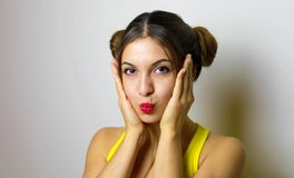 Beautiful girl with two hair chignon send kiss to the camera hol stock photography