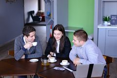 Three businessmen, woman and men discussing robot with cup of te stock image