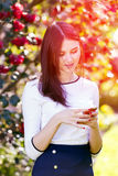 Beautiful girl typing text message on her smart phone in the gar Royalty Free Stock Image