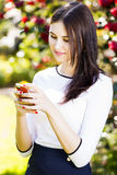 Beautiful girl typing text message on her smart phone in the gar Royalty Free Stock Images