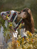 Beautiful girl in Ukrainian costume. Gathers flowers in the meadow Stock Photo