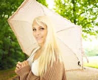Beautiful Girl With Umbrella. Beautiful busty young blonde girl with umbrella under trees in park Royalty Free Stock Photo