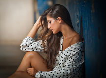 Beautiful girl with unbuttoned shirt posing, old wall with peeling blue paint on background. Pretty brunette sitting on the floor. Attractive dark long hair royalty free stock image