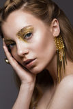 Beautiful girl in Underwear with creative gold makeup and hair. The beauty of the face. Royalty Free Stock Photography