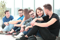 Beautiful girl University student with friends sitting on the fl Stock Image