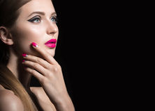 Beautiful girl with unusual black arrows on eyes and pink lips and nails. Beauty face. Royalty Free Stock Photo