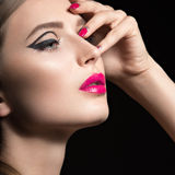 Beautiful girl with unusual black arrows on eyes and pink lips and nails. Beauty face. Picture taken in the studio on a black background Stock Photo