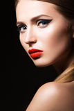 Beautiful girl with unusual black arrows on eyes and red lips. Beauty face. Picture taken in the studio on a black background Stock Photo