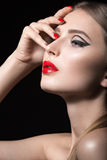 Beautiful girl with unusual black arrows on eyes and red lips and nails. Beauty face. Royalty Free Stock Photos
