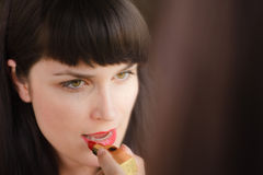Beautiful girl uses lipstick red lipstick Stock Photos
