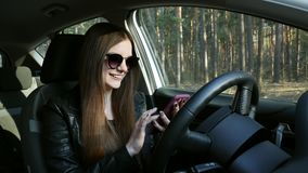 Beautiful girl uses a mobile phone in the car stock video footage