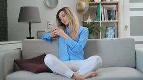 Beautiful girl using digital mobile device browsing the internet and social media, staying connected at home enjoying. Modern lifestyle. Woman using smartphone stock video