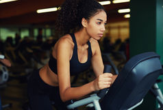 Beautiful girl using a exercise bike at the gym Royalty Free Stock Photo