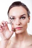 Beautiful girl using eyelash curler Royalty Free Stock Image