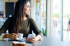 Beautiful girl using her mobile phone in cafe. Stock Photography