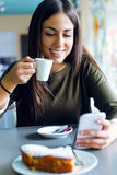 Beautiful girl using her mobile phone in cafe. Royalty Free Stock Photo