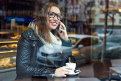 Beautiful girl using her mobile phone in cafe. Royalty Free Stock Images