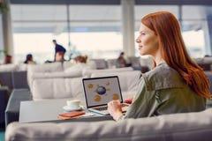Beautiful girl using laptop in airport Royalty Free Stock Image