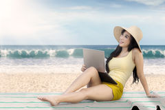 Beautiful girl using laptop on the beach Royalty Free Stock Photo