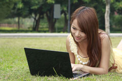 Beautiful girl using laptop on grass Royalty Free Stock Photos