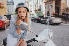 Beautiful girl is using lipstick. Sh is putting some make up on. Girl is looking at small mirror that is above control. Handles. Also she wears helmet Stock Image