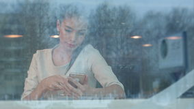 Beautiful girl using phone while drinking coffee in a cafe viewed through window stock footage