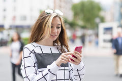 Beautiful girl using smart phone in the street, modern lifestyle Royalty Free Stock Photos