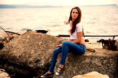Beautiful girl using smartphone sitting on an old pier Stock Photography