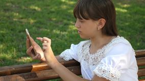 Beautiful girl using a smartphone is writing a letter on a bench in a beautiful green park. Slow motion. Young stock footage