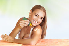 Beautiful girl using sunscreen Stock Images