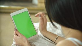 Beautiful girl using tablet with green screen lying on bed at home.  stock video footage