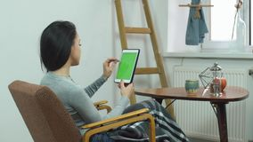 Beautiful girl using tablet with green screen, sitting on a comfortable chair at home stock video footage