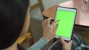 Beautiful girl using tablet with green screen, sitting on a comfortable chair at home stock video