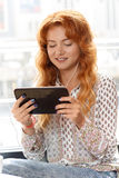 Beautiful girl using tablet. Beautiful girl listening to music on her tablet Royalty Free Stock Image