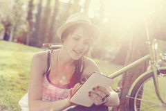 Beautiful girl using tablet in park Royalty Free Stock Image