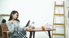Beautiful girl using tablet and sitting on a comfortable chair at home stock video