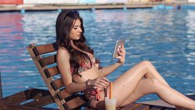 Beautiful girl using a tablet and suntanning near pool. She drinks a cocktail stock footage