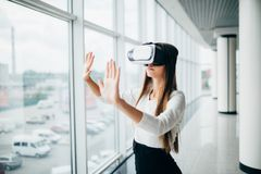 Beautiful girl using virtual reality glasses near bright window with skyscraper view outside. Business woman wearing VR goggles Royalty Free Stock Image