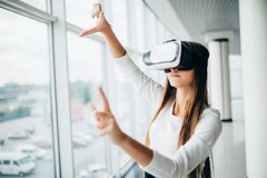 Beautiful girl using virtual reality glasses near bright window with skyscraper view outside. Business woman wearing VR goggles. And interacts with cyberspace Stock Photo